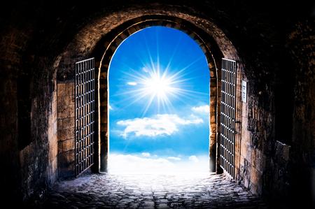 太陽にアーチの開口部に暗いトンネルの廊下。トンネルの終わりに光です。 写真素材