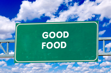 Good Food sign on the road with clouds in background photo