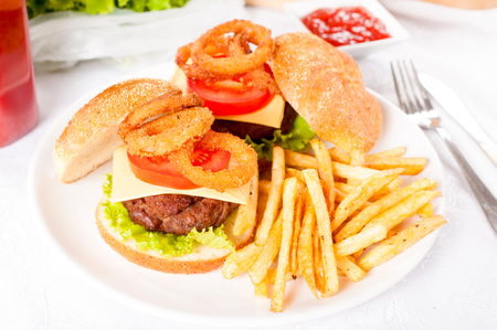 Beef burger with onion rings and french fries on the plate  photo