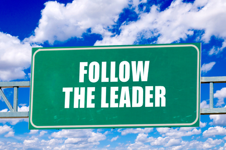 follower: Fallow the leader sign on the green board with clouds in background