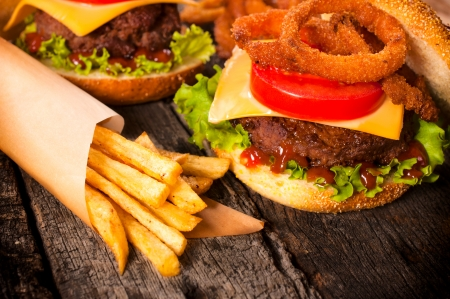 Juicy cheeseburger with onion rings and french fries  photo
