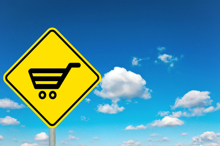 Shopping yellow road sign with clouds and sky in background photo