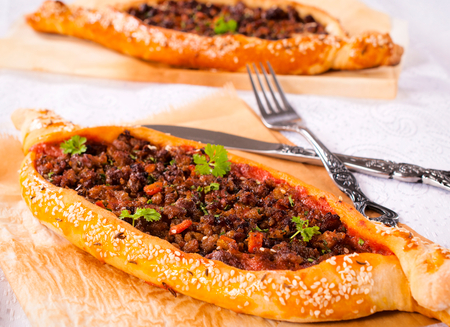 konya: Homemade traditional Turkish meal pide stuffed with meat and sauce