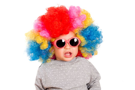 Suprised child with clown wig and sunglasses isolated on white photo