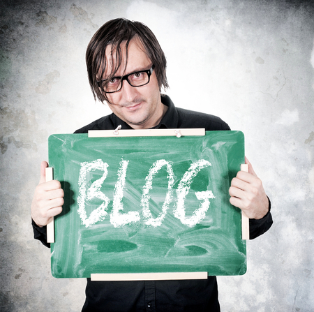 Man holding chalkboard with blog sign photo