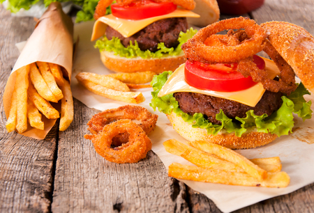 Onion rings,french fries and cheeseburger on the wooden table photo