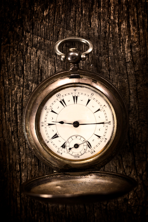timeless: Old pocket watch on the wooden background.Selective focus in the middle of watch