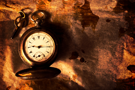timeless: Golden pocket watch on the old paper with blank space on right side.Selective focus on the watch Stock Photo