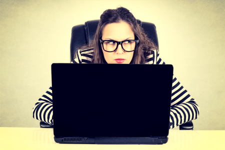 private detective: Suspicious businesswoman siting on the desk with laptop computer Stock Photo