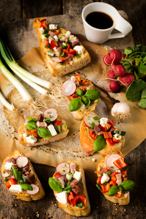 Selective focus on the three front bruschettas with cheese and vegetables  photo