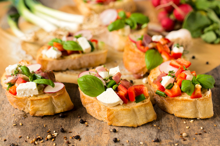 Selective focus on the fresh baked bruschetta with cheese and vegetables in the middle  photo