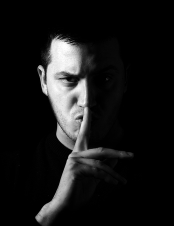 Man showing be quiet sign, low key and black and white techniques  photo