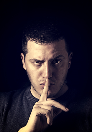 shush: Man showing the sign of silence,low key technique