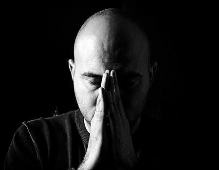 Young man praying in the dark,low key