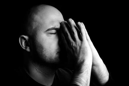 Man alone praying,low key and monochrome