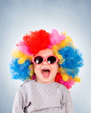 Positive child with sunglasses and clown wig isolated on blue background  photo