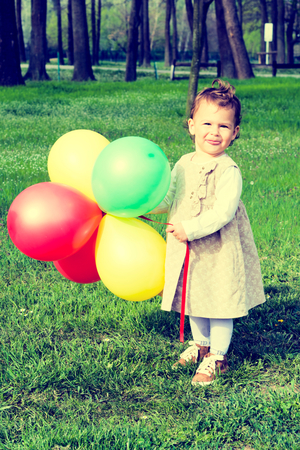 Little child holding colorful balloons outdoor.Selective focus on the child  photo