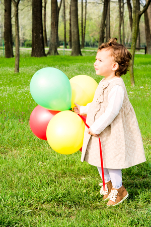 Little girl holding colorful balloons.Selective focus on the child  photo