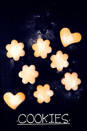 Heart and star shape cookies on the black wooden  from above photo