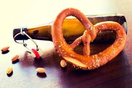 Bottle of beer and fresh baked pretzel.Selective focus in the middle of pretzel photo