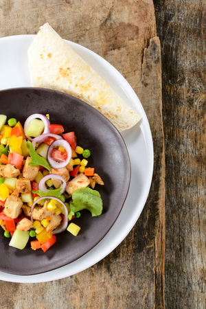 Fresh chicken salad and tortilla bread.Blank space on the right side on wooden background  photo