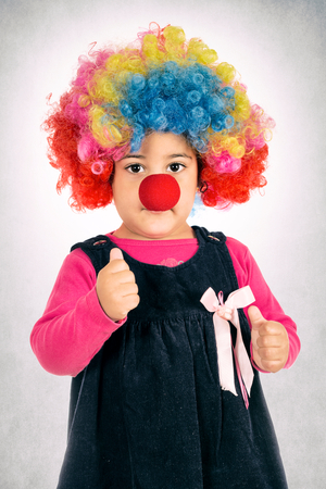Little child with clown mask holding thumb up photo