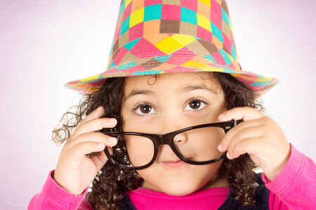 Confused little child with colorful hat looking up photo