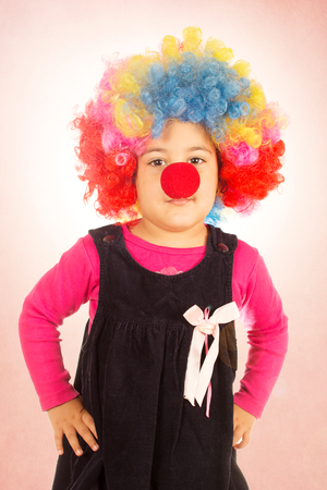 Little child with colorful clown wig and red nose  photo
