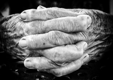 black jesus: Very old woman holding her hands together,black and white Selective focus on the front part of hands Stock Photo