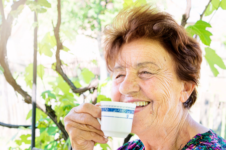 Old female drink coffee and smile in backyard photo