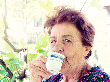 Old woman drink coffee and smile in backyard photo
