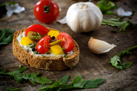 Selective focus on the vegetarian bruschetta with cheese cream,bell pepper,olives and cherry tomato photo