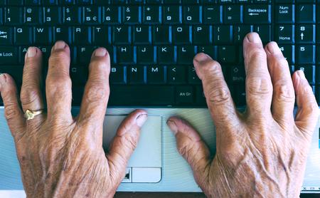 teclado de computadora: Antiguo manos que pulsan en el teclado de la computadora desde arriba Foto de archivo