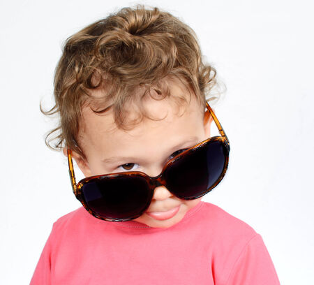 astonished: Funny little child with sunglasses on white background