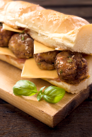 hero sandwich: Big sandwich with meatball on the wooden board.Selective focus on the front meatball