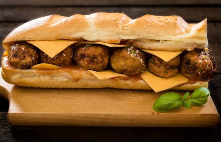 hero sandwich: Big and juicy meatball sandwich on the wooden background  Stock Photo