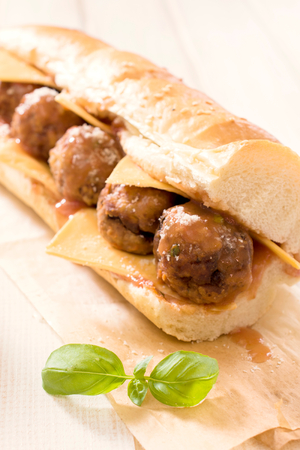 hero sandwich: Submarine sandwich stuffed with meatballs and tomato sauce.Selective focus on the front meatball Stock Photo