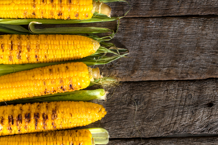 Grilled young corn on the wooden background with blank space on right side  Stock Photo