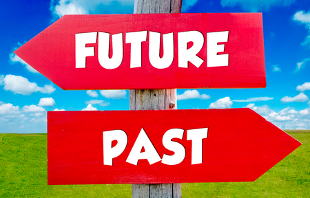 Future and past concept on the red signs with landscape in background photo