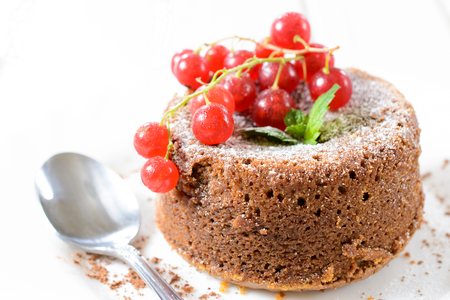Sweet lava cake with red currants.Selective focus in the middle of cake photo