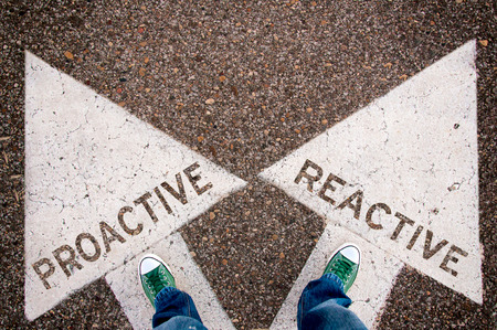 active arrow: Proactive and reactive dilemma concept with man legs from above standing on signs Stock Photo