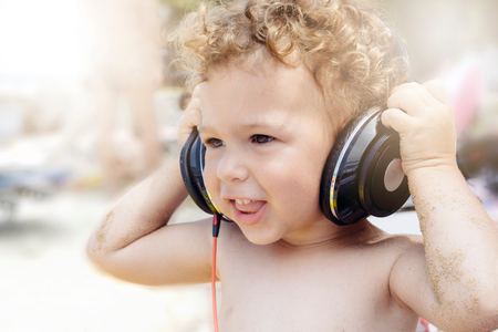 aciculum: Little child holding headphones on head and listen music .Selective focus on the child Stock Photo
