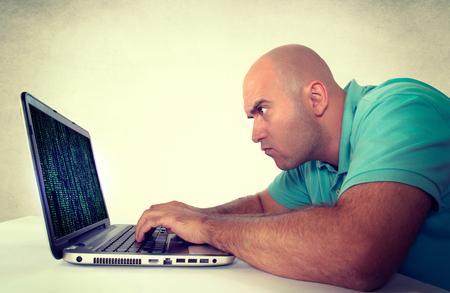 Bald man programming on his laptop photo