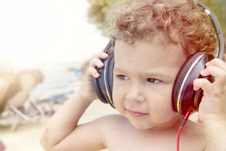 adn: Chald sosteniendo auriculares adn lisne la m�sica Little, enfoque selectivo Foto de archivo