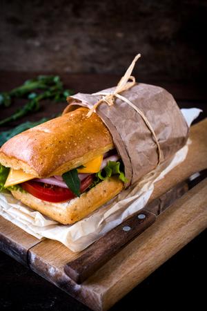 panino: S�ndwich rellenos de jam�n y queso en la tabla de madera, enfoque selectivo Foto de archivo