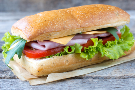 Single Italian panini sandwich on the wooden background,selective focus  Banco de Imagens