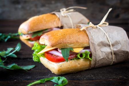 Sandwichs panini populares con jamón y queso en el fondo de madera, enfoque selectivo