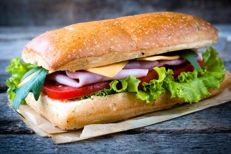 Popular Italian panini sandwich with ham on wooden background,selective focus photo