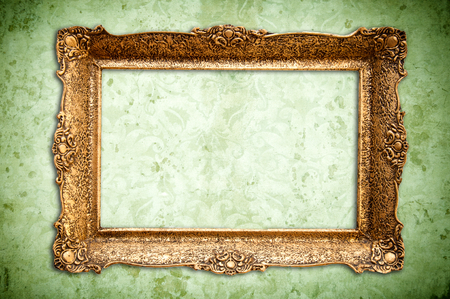 grunge floral faded wallpaper with golden vintage empty frame photo