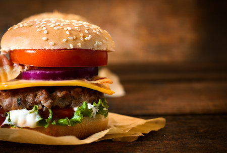 Close up to beef burger with cheese and vegetables.Blank space for text on the right side